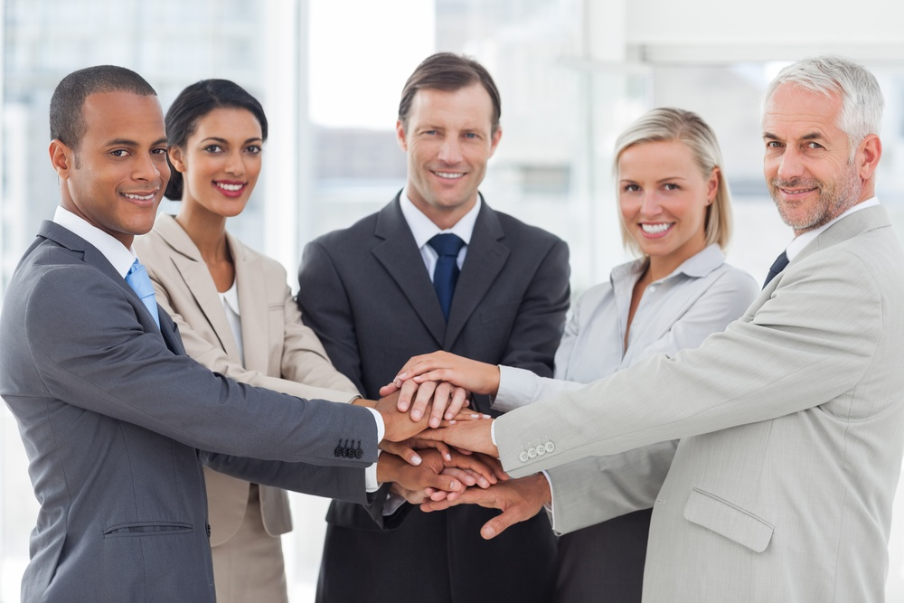 Group of smiling business people piling up their hands together in the workplace.jpeg