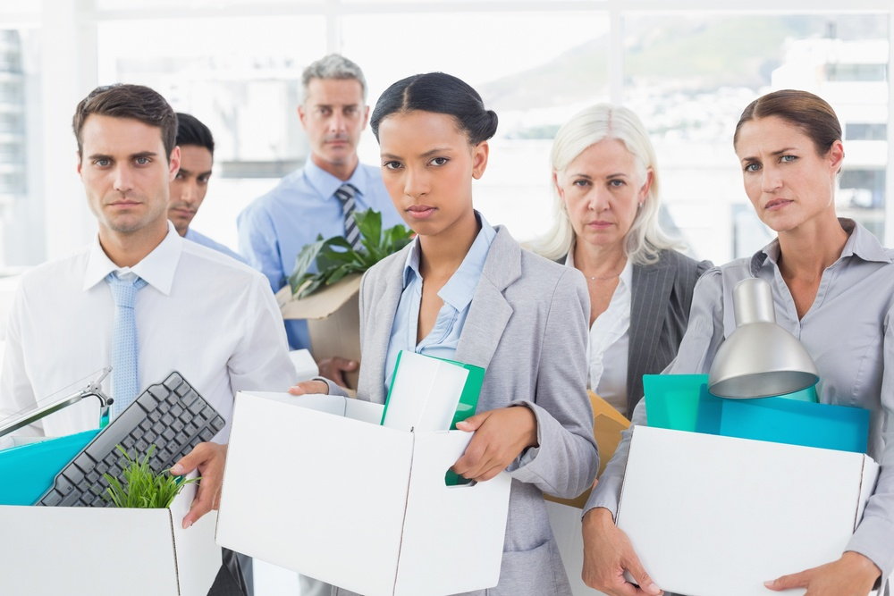 Unhappy fired business people holding box in office.jpeg