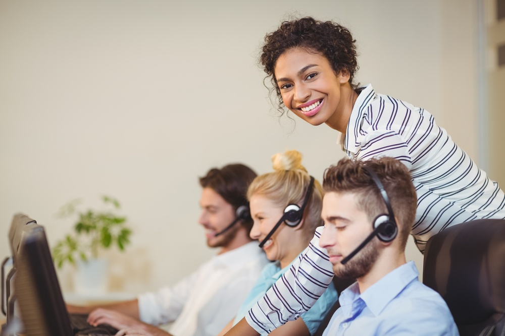 Portrait of smiling businesswoman with employees in call center.jpeg