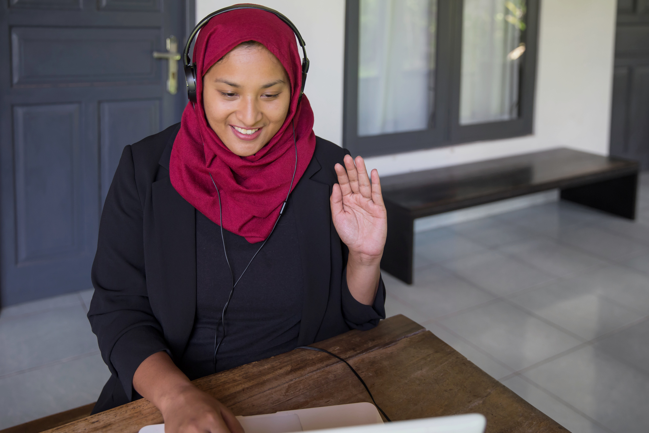 woman in a hijab waves during a zoom interview