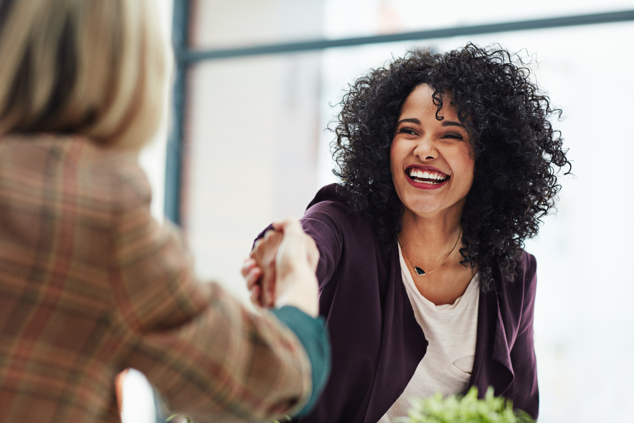 Woman shaking hands with hiring manager after successful interview