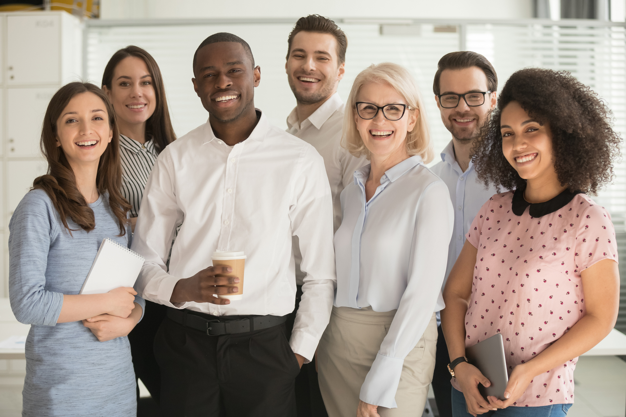 Group of office employees smiling and looking motivated