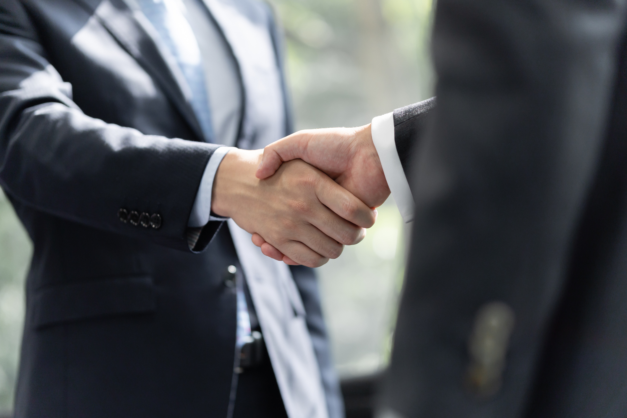 two businessmen shaking hands, signaling a partnership