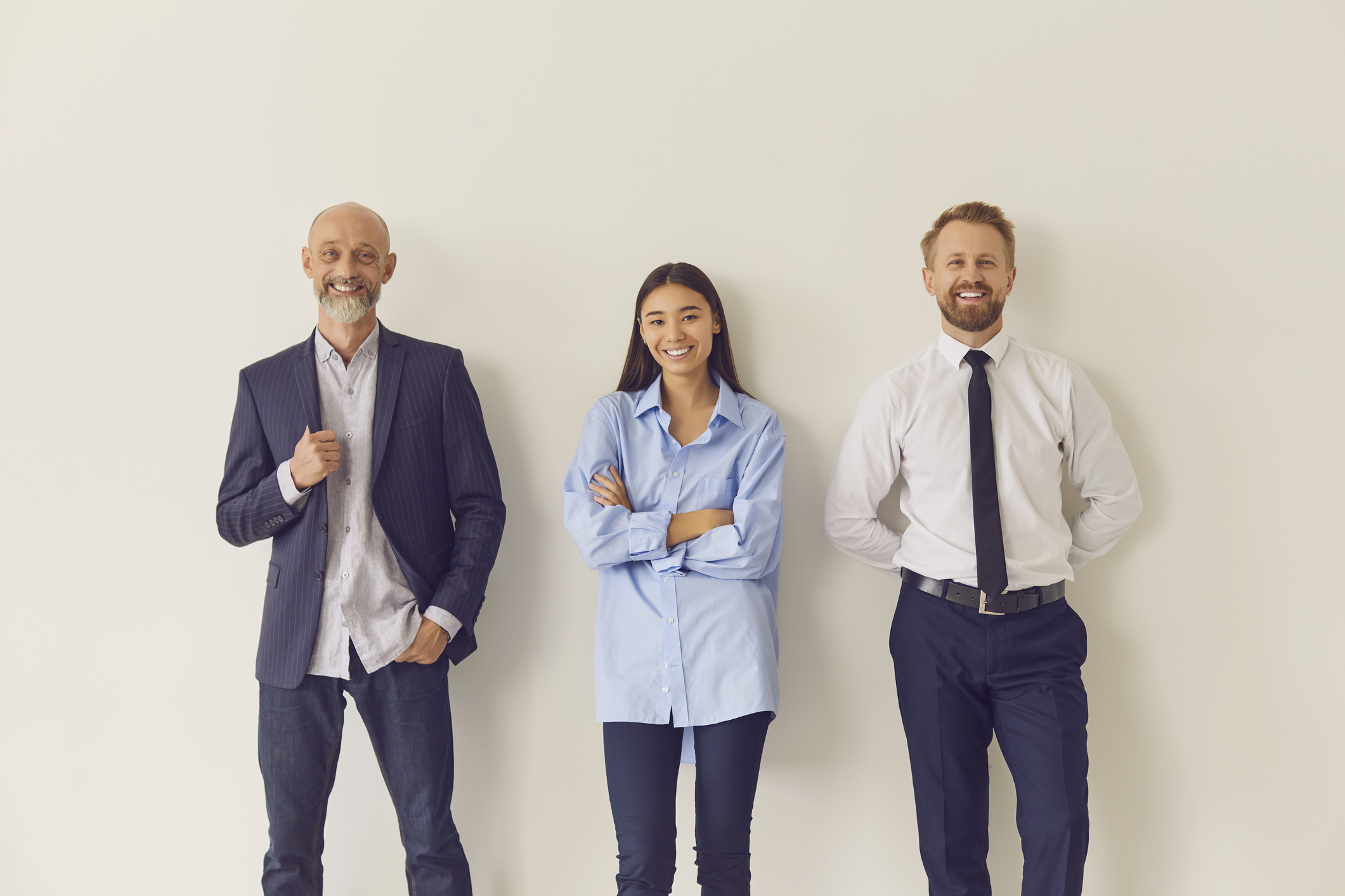 Three business people smiling; each one part of a different generation