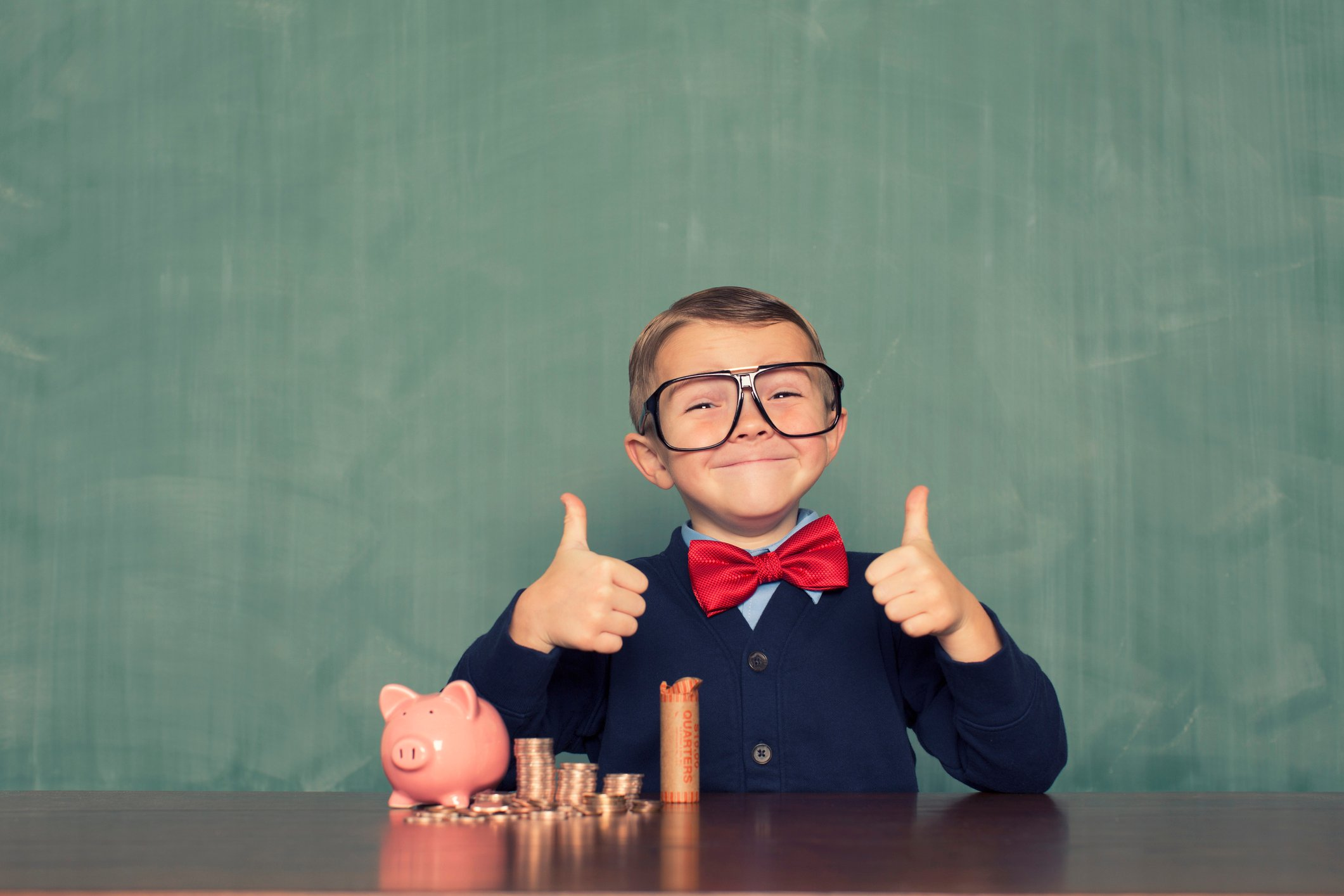young boy giving thumbs up with piggy bank and piles of coins