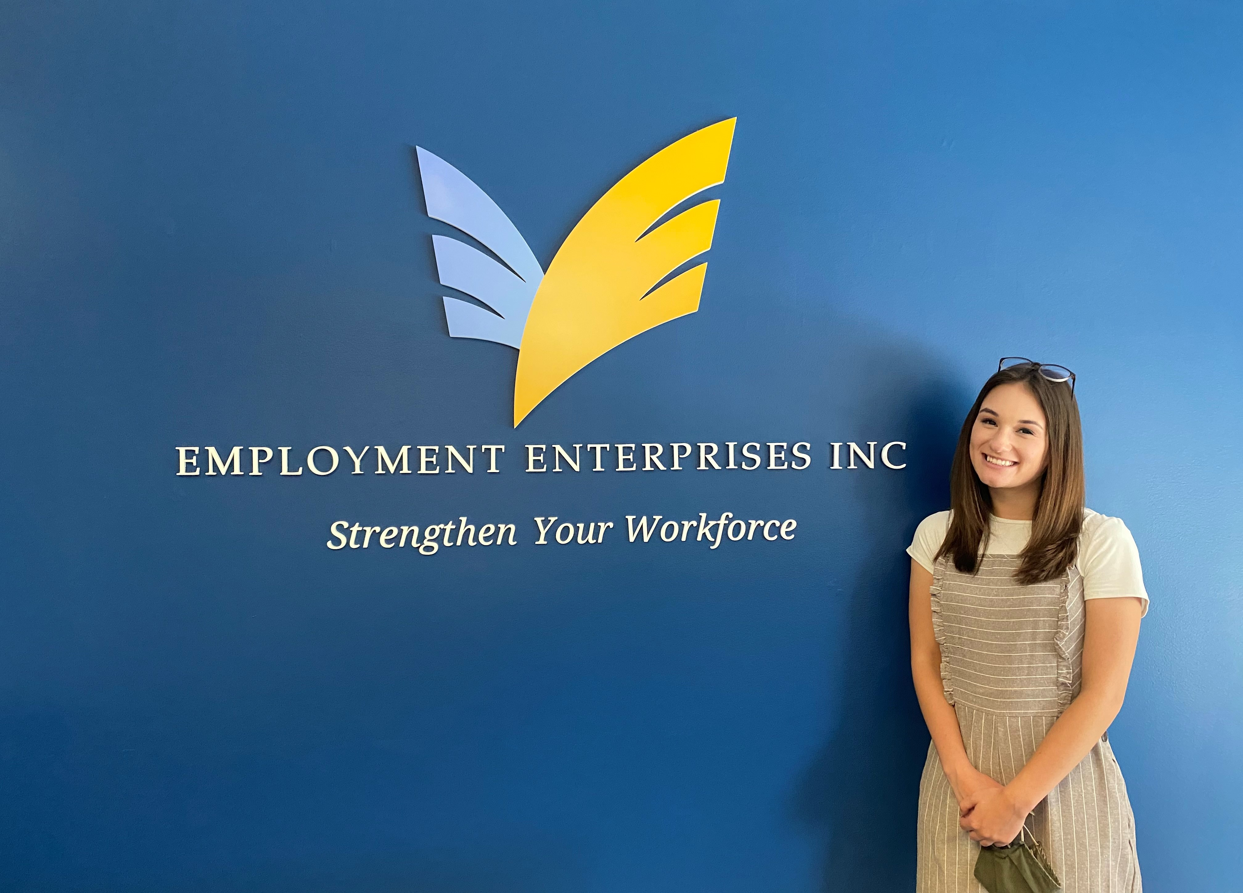 Sadie smiling in front of an Employment Enterprises, Inc. sign
