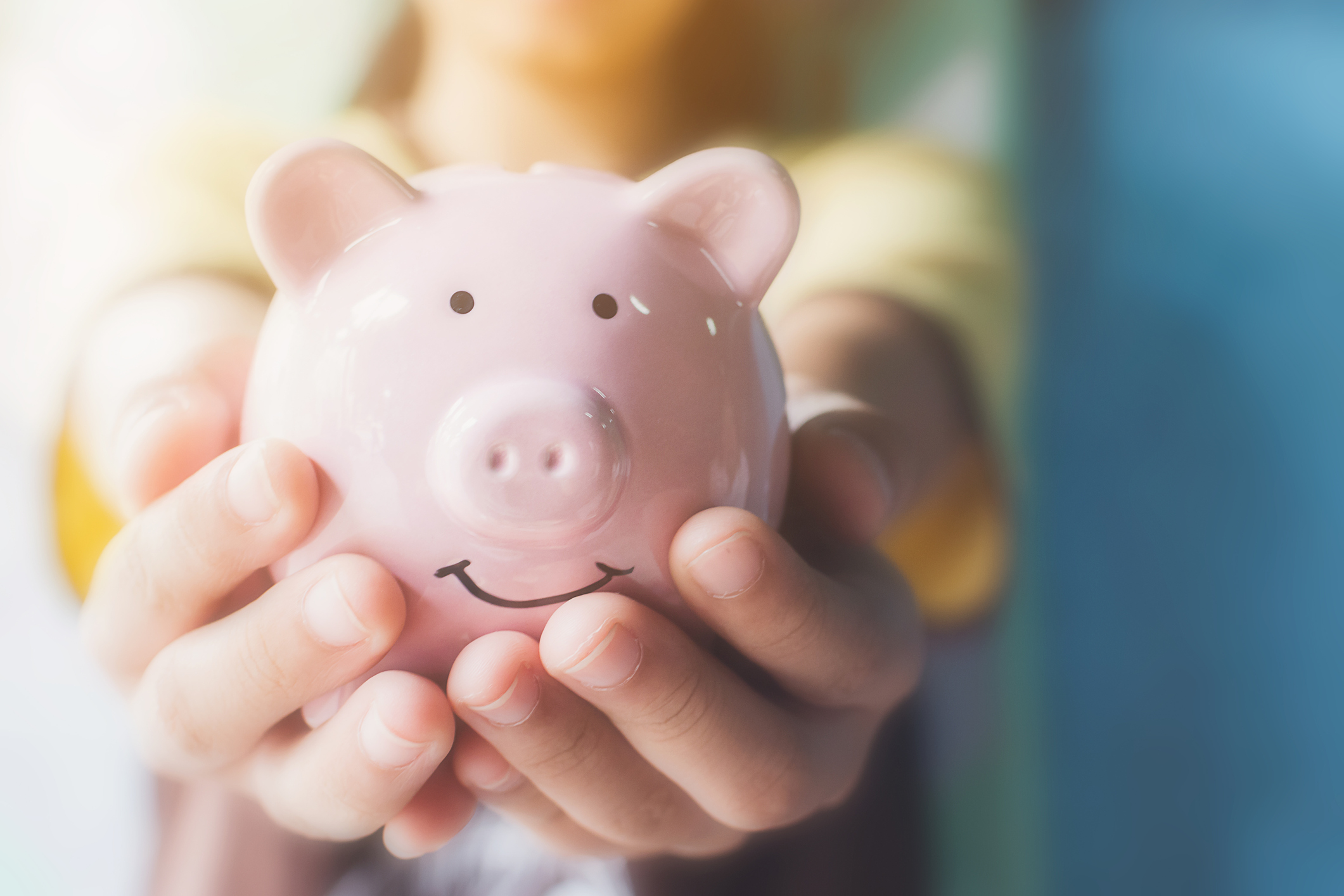 Woman holding a light pink piggy bank in the palms of her hands. Being prepared to discuss your desired salary can pay off!